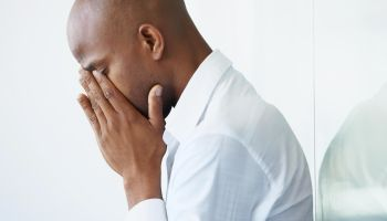 A young businessman crying with his face in his hands