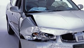 Silver sedan with front end damage and deployed airbags