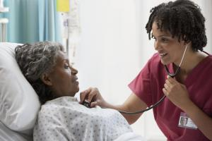 African nurse using stethoscope on hospital patient