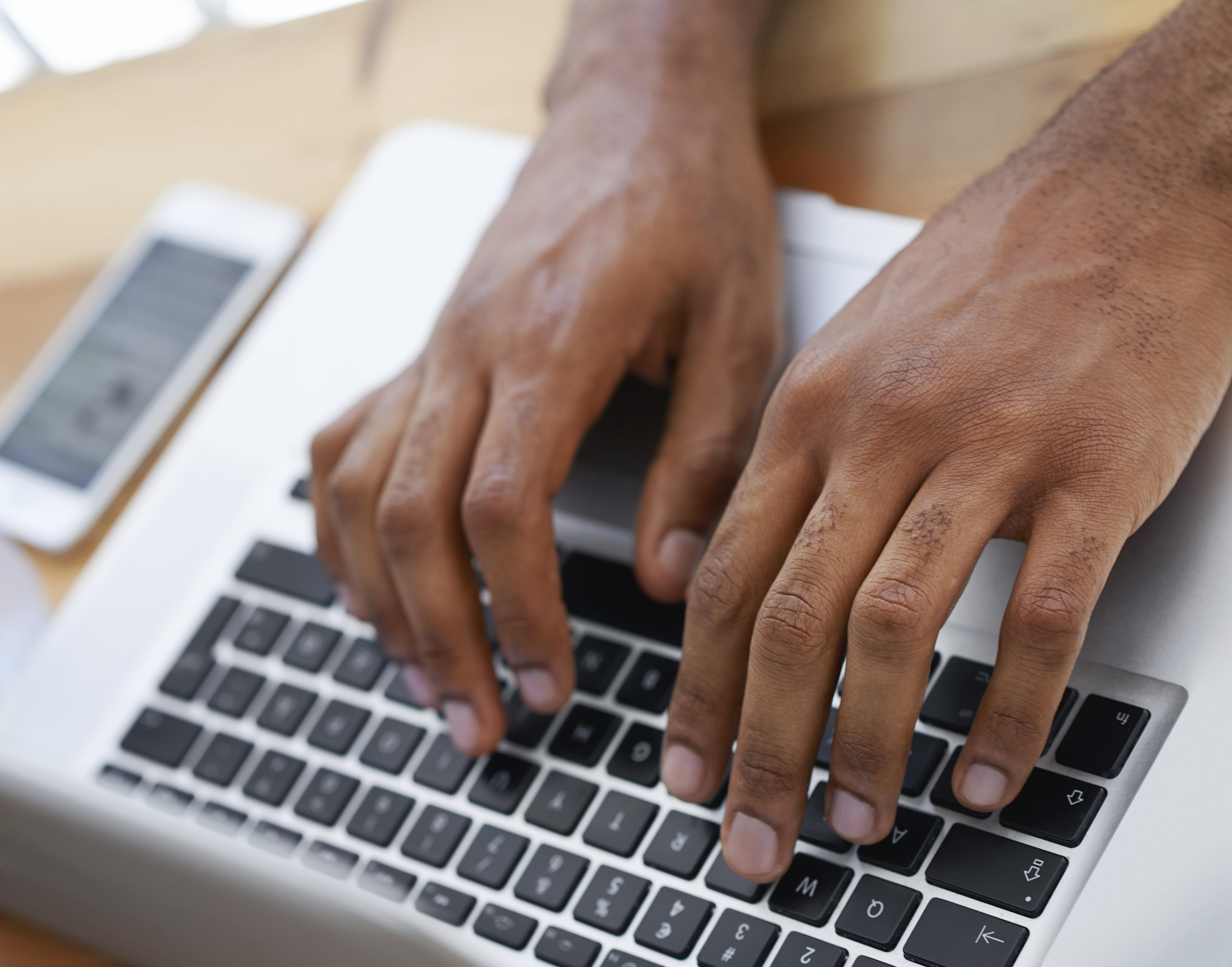 Cropped view of a businessman's hands as he types on his laptop