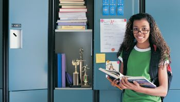 Portrait of a Successful Schoolgirl Standing Next to an Open Locker With Trophies Inside
