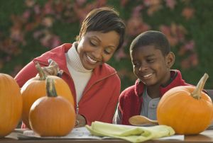 African mother and son carving pumpkins