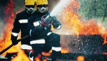 Firefighters Holding a Hose and Spraying Water