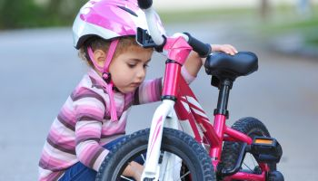 Girl, aged 3, fixes bicycle