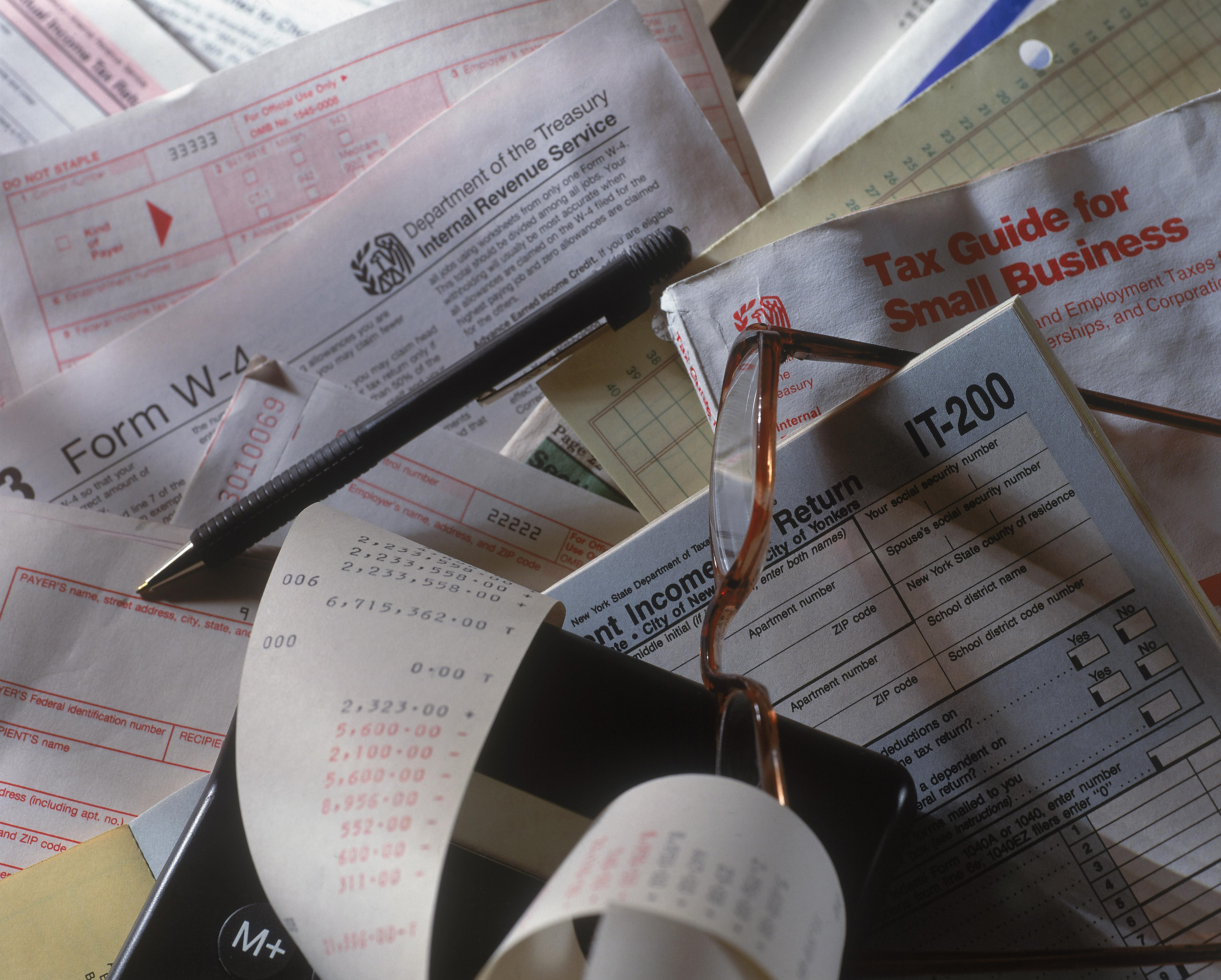 Tax forms, pen and glasses, close-up