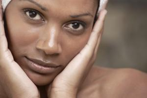 Closeup of an african beauty holding her face in her hands - Skincare & Beauty