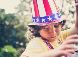 Patriotic boy wearing a hat and beads.