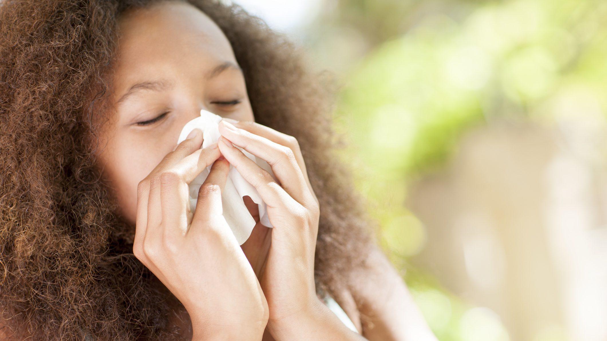 Teenage girl sneezing.