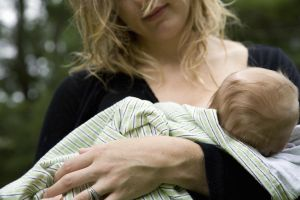 Mother breastfeeding baby girl (2-4 months) outdoors, mid section