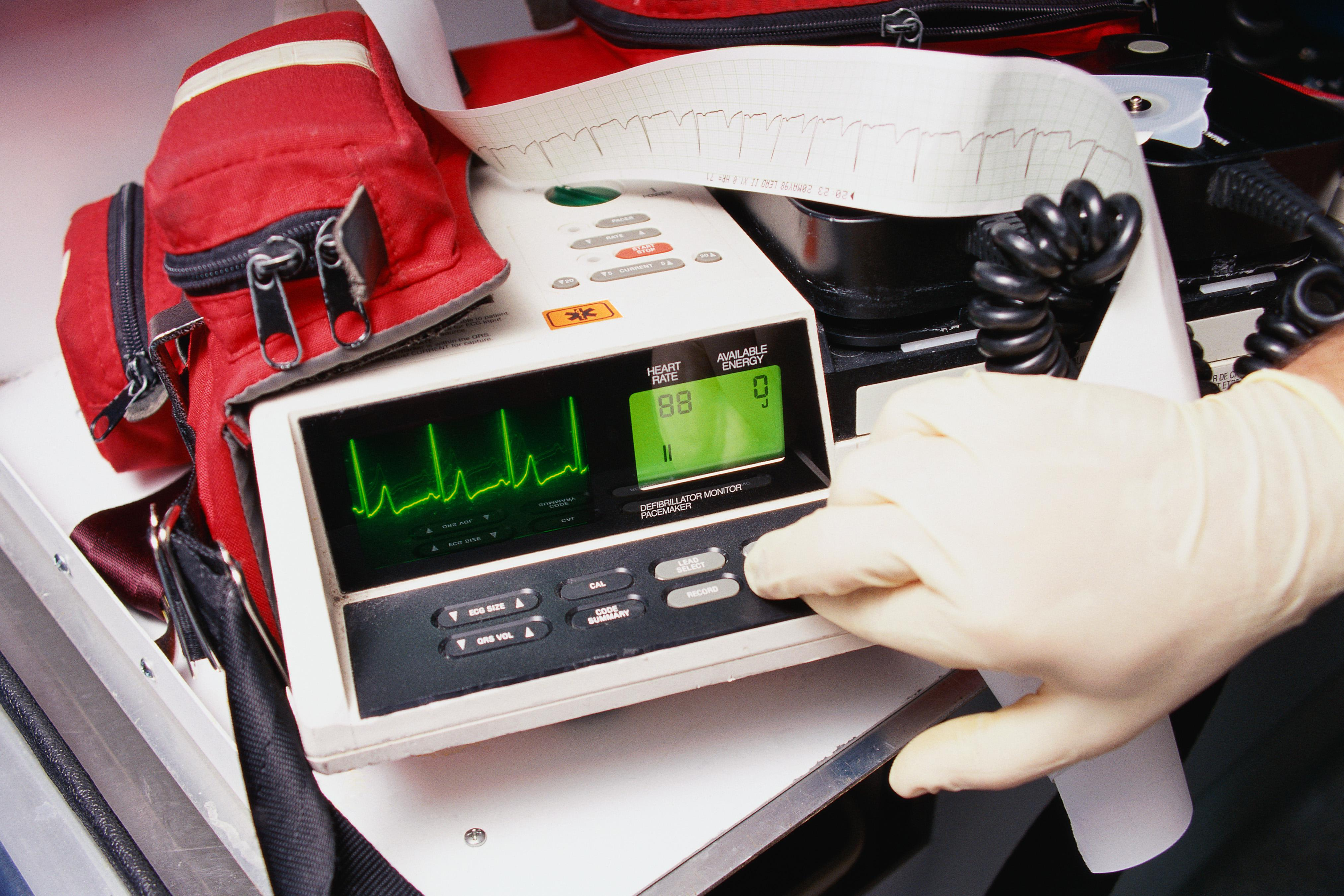 Hand in rubber glove pressing button on defibrillation monitor