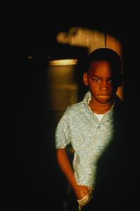 Boy (6-8) with sad look on face, surrounded by shadows