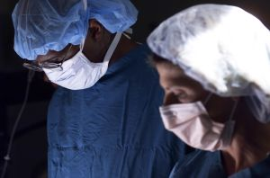 a male doctor and a female nurse work together in during an operation
