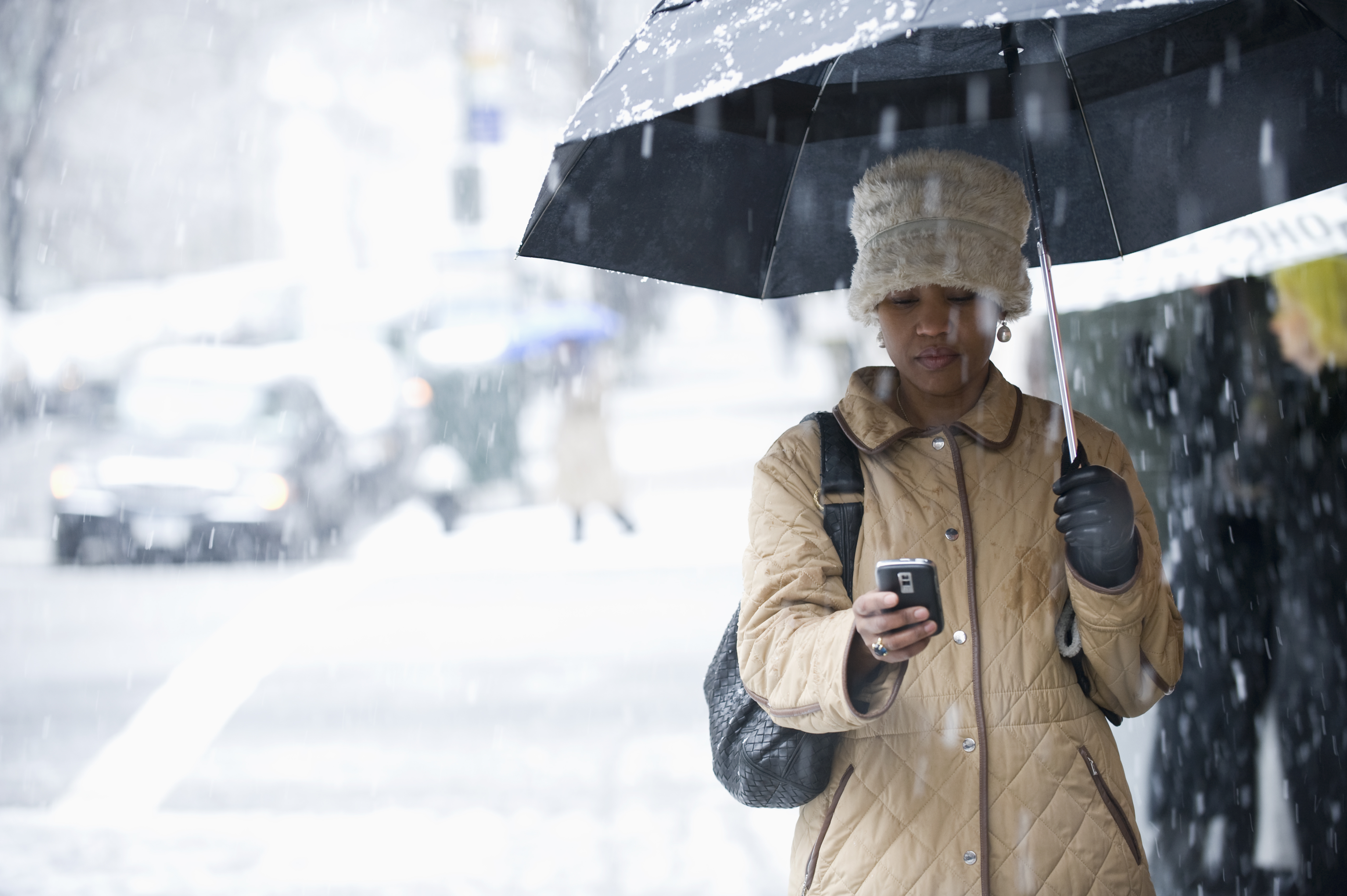 Black woman text messaging in the rain