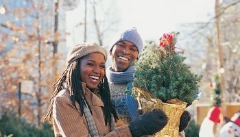 Young Couple Standing in a City Street Holding a Small Christmas Tree