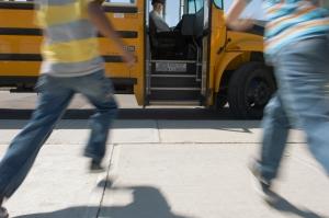 Schoolchildren running to schoolbus