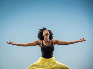 Black woman dancing with arms outstretched