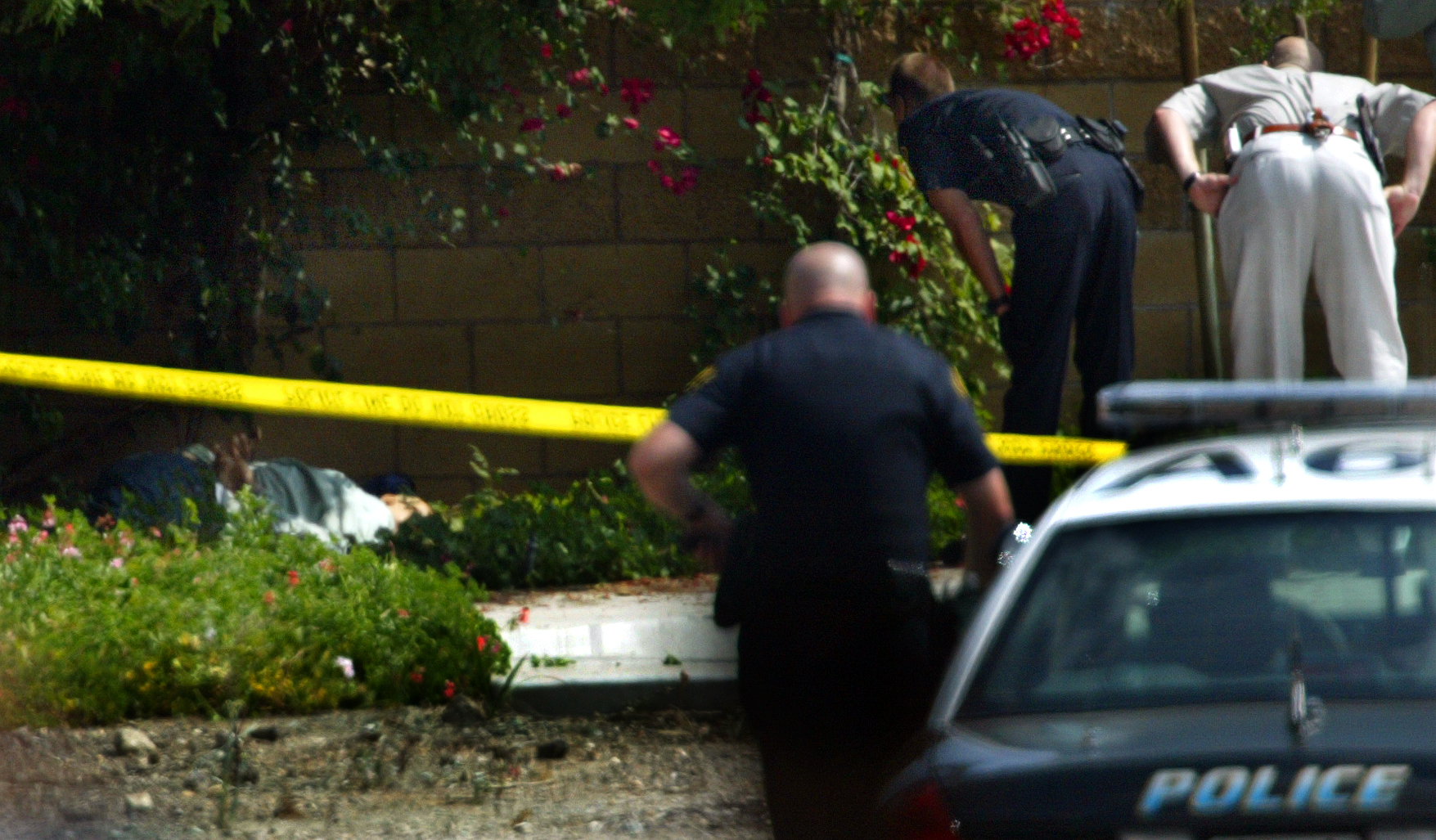 Arcadia and El Monte police investigate the scene where an armed bank robber was shot and killed by