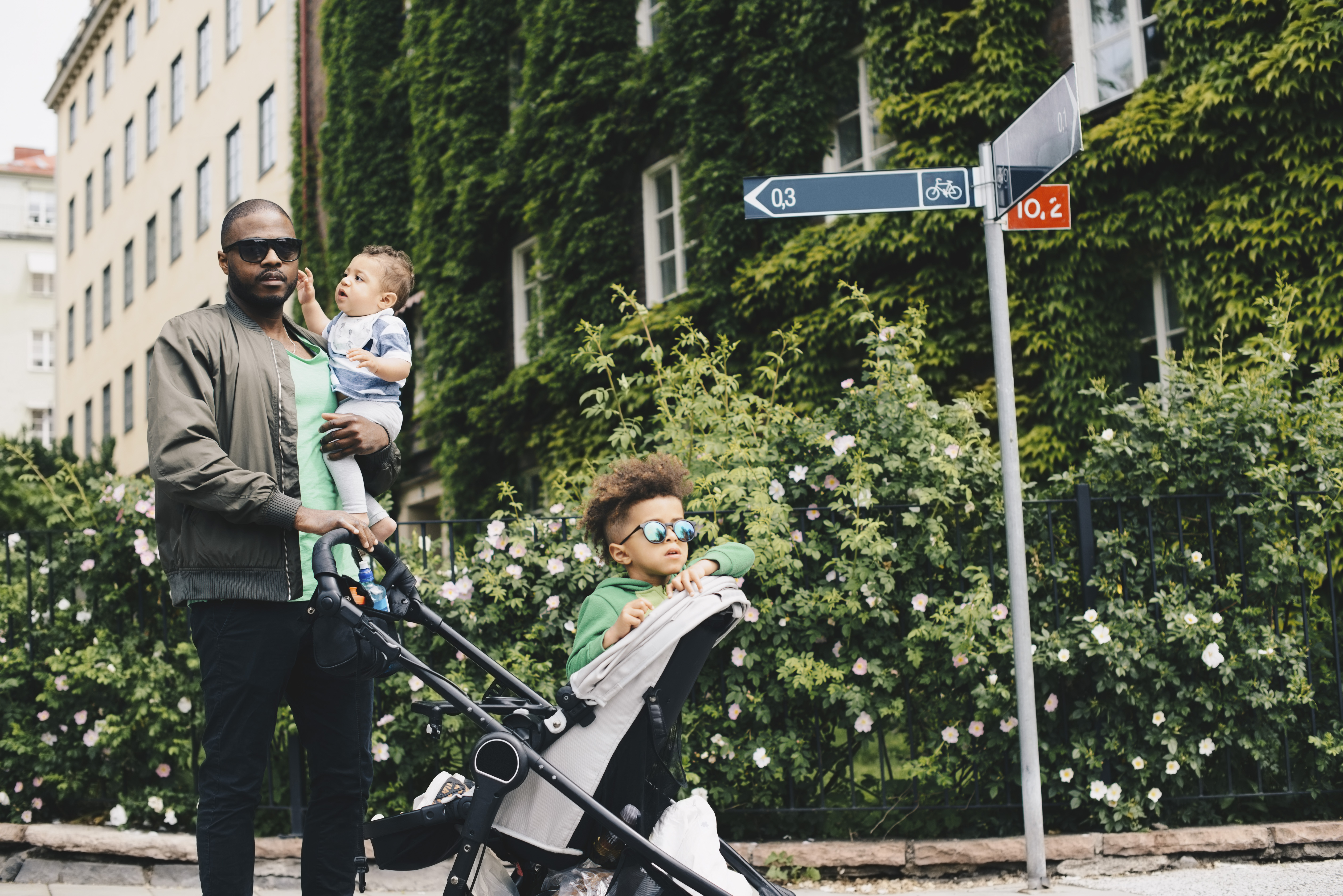Father walking with children while pushing baby stroller against plants in city