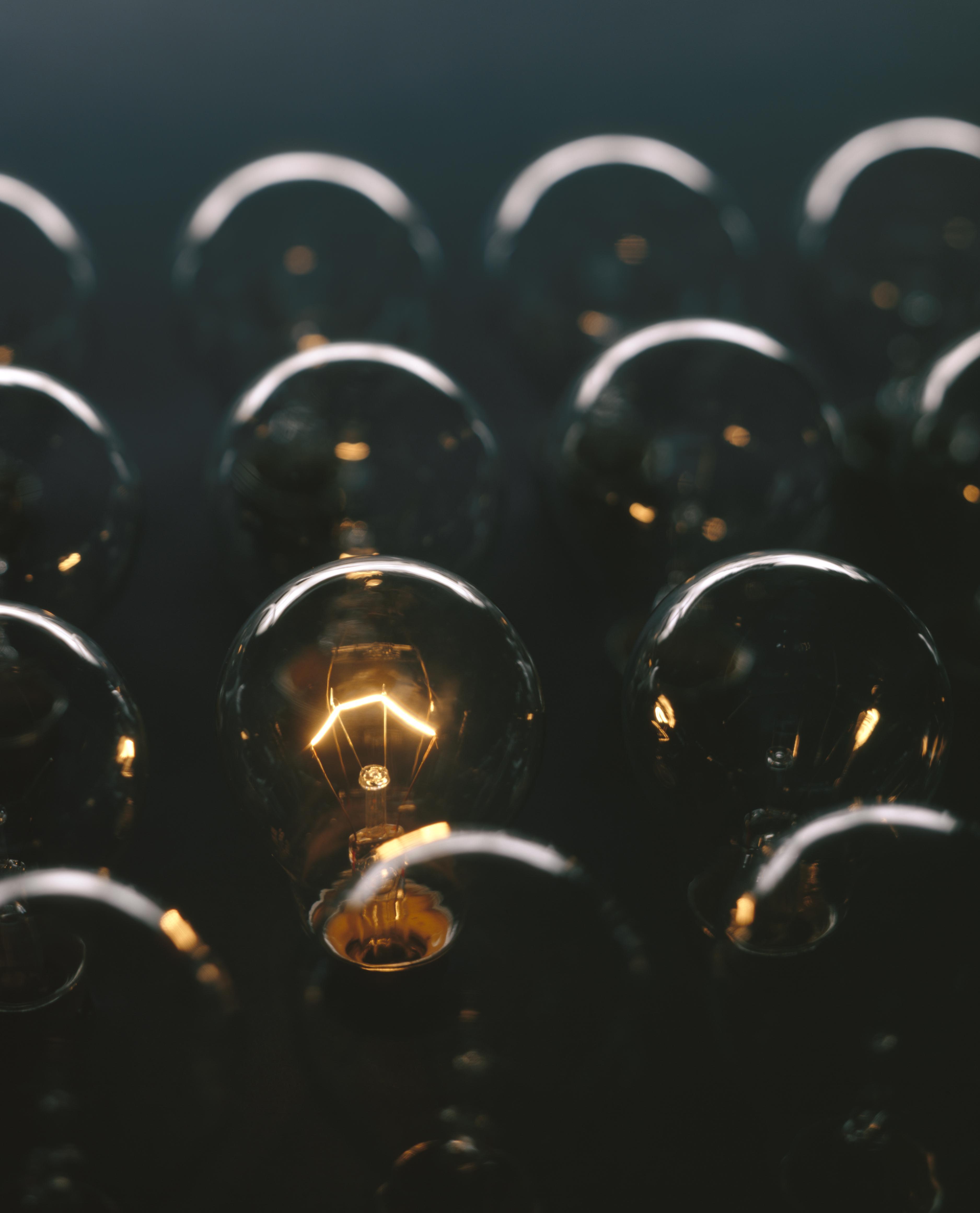 Glowing light bulb against dark background