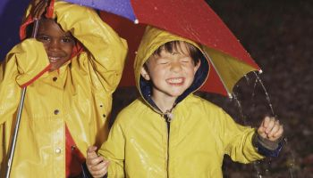 Boys playing in rain under umbrella