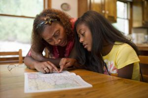 African American teen looks at map with mom
