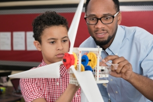 Teacher helping student with model wind turbine