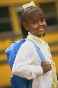 Girl with backpack by school bus