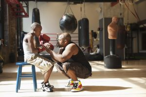 Father talking to son wearing boxing gloves