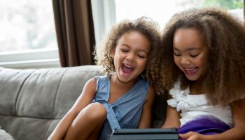 Mixed race girls using digital tablet on sofa
