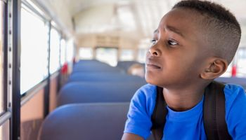 Young boy worriedly looks out bus window