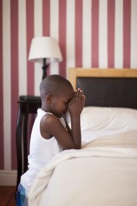 African boy saying prayers at bedside