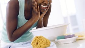Young woman bent over bowl, washing face, smiling